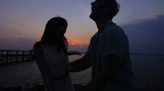 Silhouette of young happy loving couple hanging out on their beach holiday  Stock Footage