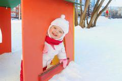 Happy little girl plays in bright small house on playground Stock Photos