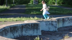Little beautiful girl runs on old abandoned fountain in summer park Stock Footage