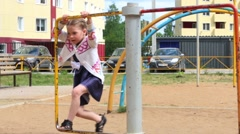 Llittle girl in dress plays on children playground at summer day Stock Footage