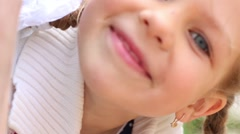Pretty little girl peek out from pipe on playground at summer day Stock Footage
