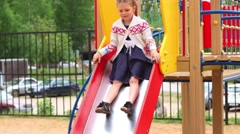 Llittle girl in dress slides on playground at summer day Stock Footage