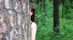 Pretty woman peeking out from behind tree in green summer forest Stock Footage