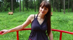 Pretty young woman on carrousel in green summer forest at sunny day Stock Footage