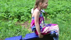 Little girl does abs exercises on outdoor exerciser in green park Stock Footage