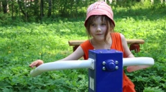 Little girl trains on outdoor exerciser in green summer park Stock Footage