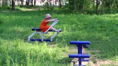 Little girl does exercises on outdoor exerciser in green park Stock Footage