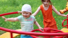 Two little girls with big balloon on roundabout in green forest at summer day Stock Footage