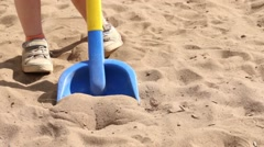 Toy shovel and feet of little boy going on sand at summer Stock Footage