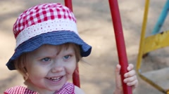 Little happy girl in hat swings on children playground at spring day Stock Footage