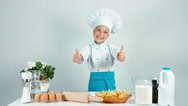 Portrait cute smiling chef cook girl enters the frame and standing at kitchen Stock Footage