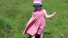 Happy little girl goes on green grass on meadow at sunny summer day Stock Footage