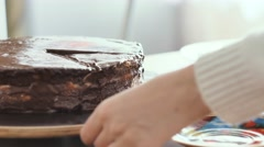 Girl cuts a piece of chocolate cake, and puts it on a plate close-up shot Stock Footage