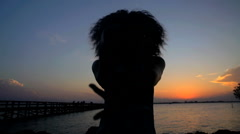 Silhouette of young beautiful African American girl chilling and dancing Stock Footage