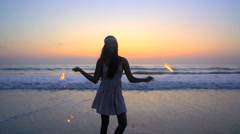 Silhouette of happy young Asian Indian girl having fun with sparklers at beach Stock Footage