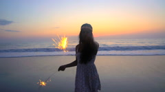 Silhouette of Indian American female enjoying New Years Eve party with sparklers Stock Footage