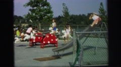 1972: many children are at playground playing on equipment such as teeter totter Stock Footage