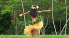 Polynesian Tahitian girl in grass skirt and flower headdress dancing hula style Stock Footage