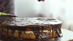 Female hand pour the chocolate cream on the cake and begin to spread Stock Footage