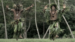 Young Tahitian males performing warrior style hula dance outdoors barefoot  Stock Footage