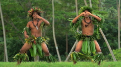 Barefoot Tahitian male men in hula skirts and flower headdress performing  Stock Footage