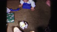 1972: twin babies crawling around on the floor playing with toys on christmas Stock Footage