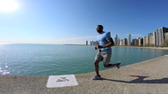 Ethnic African American male running along Lake Michigan shoreline for fitness Stock Footage