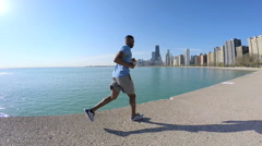 Ethnic African American male running in the city for sport and fitness Chicago Stock Footage