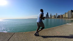 Athletic Ethnic African American male running in city by Lake Michigan Chicago Stock Footage