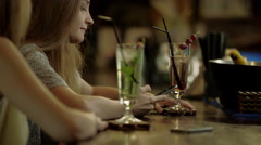 Women gossiping sitting in a bar Stock Footage