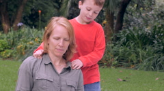 A nervous mother is concerned while her son touches her shoulders - slowmo Stock Footage