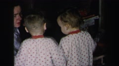 1972: two toddlers in matching pajamas looking at new toys with mother helping Stock Footage
