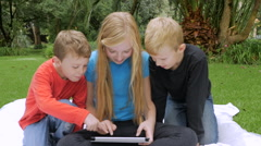 Three young children play together on a single tablet outside - slowmo handheld Stock Footage
