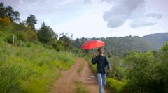 A man with a beard and a red umbrella walking on dirt road Stock Footage