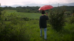 A man with a red umbrella walks off into the distance in a rural setting Stock Footage
