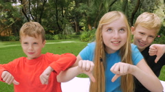 Three children look at the camera and give the thumbs down and laugh in slowmo Arkistovideo
