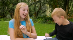 Blond boy and girl tickle each other and smile at the camera - slowmo Stock Footage