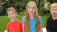 Three young children roll their eyes and look at the camera - slowmo Stock Footage
