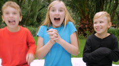 A young girl shows excitement and surprise while two boys imitates her Stock Footage