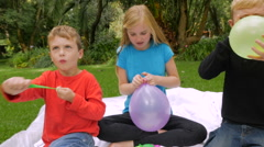 Three young kids blow up and tie off balloons outside - slowmo handheld Stock Footage