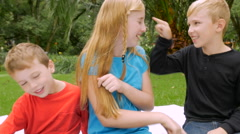Three siblings poking and tickling each other outside - slowmo handheld Stock Footage