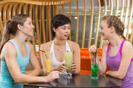 Three Women Drinking Juice Chatting in Sport Cafe Stock Photos