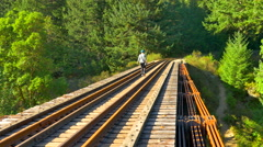 4K Woman Walks Across Old Wooden Rail Road Trestle, Tracks and Wood over River Stock Footage