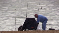 Fisherman fishing on many fishing rods on the lake Stock Footage