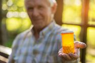 Male hand holds pill bottle. Stock Photos