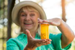 Smiling woman with pill bottle. Stock Photos