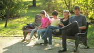 Parents with children sitting on the bench and use mobile smartphones Stock Footage