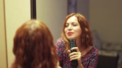 Red-haired woman singing about mirror Stock Footage