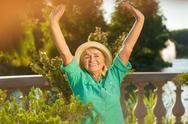 Senior woman with raised arms. Stock Photos