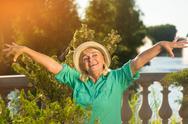 Senior lady with raised arms. Stock Photos